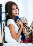 Sick teenage girl with hot tea and medication indoors Stock Photography