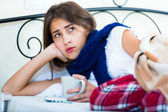 Sick teenage girl with hot tea and medication indoors Royalty Free Stock Photography