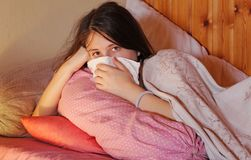 A sick teenage girl lies in bed stock photography