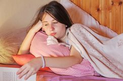 A sick teenage girl lies in bed. Gloomy stock photography