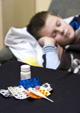 Sick teenager. An ill teenager boy in bed covered with a blanket. Focus on the medicines on the table Royalty Free Stock Images