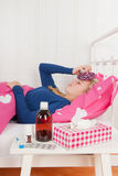 Sick teenager girl with headache. Sick teen girl laying in bed with medicine in front (focus on girl) and cooling on head against headache Royalty Free Stock Image