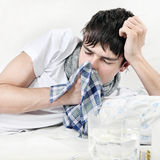 Sick Teenager with Handkerchief. Young Man with Flu on the Bed with Handkerchief Royalty Free Stock Photos
