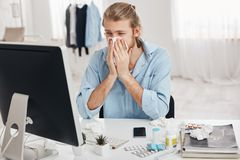 Sick and tired bearded office worker has suffering expression, has running nose, sneezing, coughing, because of flu. Sick and tired bearded male student or royalty free stock photo