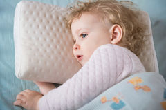 Sick and tired girl liying in bed on pillow Stock Photography