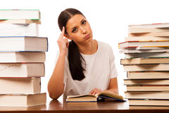 Sick and tired woman reading behind the table between two pile o Stock Images