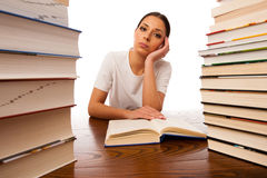 Sick and tired woman reading behind the table between two pile o Stock Photography