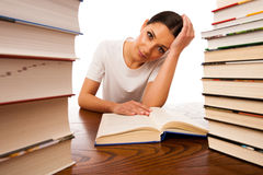 Sick and tired woman reading behind the table between two pile o Royalty Free Stock Images