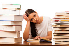 Sick and tired woman reading behind the table between two pile o Stock Photos