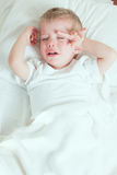 Sick toddler boy crying in bed Stock Photos