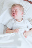 Sick toddler boy crying in bed Royalty Free Stock Images