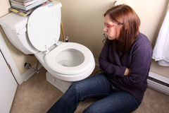 Sick by toilet. Young woman is sick by toilet royalty free stock photo