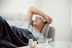 Sick wasted man lying in sofa suffering cold and winter flu virus having medicine tablets in health care concept looking royalty free stock image