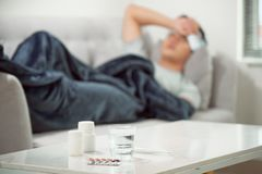 sick wasted man lying in sofa having medicine tablets royalty free stock images