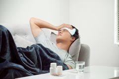 Sick wasted man lying in sofa suffering cold and winter flu virus having medicine tablets in health care concept looking stock photos