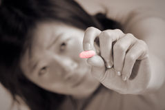 Sick woman. Holding pill with pain face Stock Image