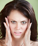 Sick Woman. Woman holds head with both hands over green background Stock Images