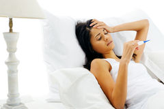 Sick woman. Lying in bed with thermometer and fever. unhappy face isolate on white baclground Royalty Free Stock Photography