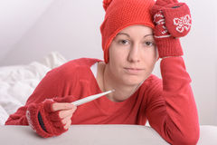 Sick woman. With thermometer in red warm clothes Stock Image