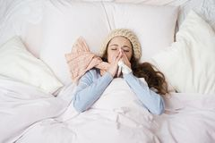 Sick woman. Lying in bed with high fever. She is blowing nose Stock Images