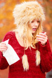 Sick woman in autumn park sneezing into tissue. Stock Images