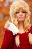 Sick woman in autumn park sneezing into tissue. Royalty Free Stock Photography