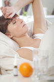 Sick woman in bed Stock Images
