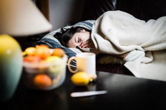 Sick woman in bed,calling in sick,day off from work.Thermometer to check temperature for fever. Vitamins and hot tea in front.Flu.Woman Caught Cold.Virus.Sick Stock Images