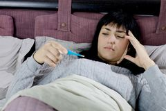 Sick woman in bed checking fever with thermometer Stock Photos