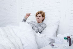 Sick woman in bed checking temperature with thermometer feverish weak suffering cold winter flu virus Stock Photos