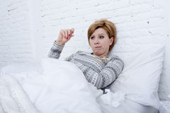 sick woman in bed checking temperature with thermometer feverish weak suffering cold winter flu virus Royalty Free Stock Photos