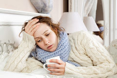 Sick woman in bed. Sick woman with cup of tea. Closeup image of young frustrated sick woman in knitted blue scarf holding a cup of tea while lying in bed. hand Royalty Free Stock Image