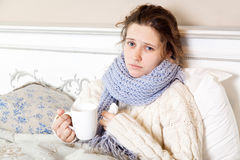 Sick woman in bed. Sick woman with cup of tea. Closeup image of young frustrated woman in knitted blue scarf holding a cup of tea while sitting in bed of her Royalty Free Stock Photography
