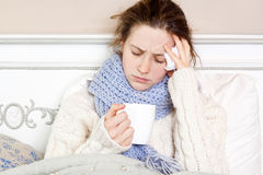 Sick woman in bed. Sick woman with cup of tea. Closeup image of young frustrated woman in knitted blue scarf holding a cup of tea while sitting in bed of her Stock Photos