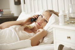 Sick Woman In Bed At Home Talking On Phone Stock Photo
