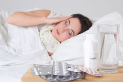 Sick woman in bed and pills on the table Royalty Free Stock Image