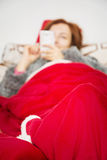 Sick woman in bed playing with her mobile phone Stock Image