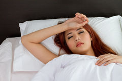 Sick woman on bed Stock Images