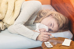 Sick woman in bed sneezing in tissue. Stock Images