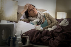 Sick woman in bed suffering flu headache Stock Image