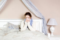 Sick woman in bed. Sick woman with terrible sore throat. Closeup image of young woman with red nose in bed with thick scarf and touching her neck and head Royalty Free Stock Photos
