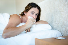 Sick woman in bed wiping her nose Royalty Free Stock Images
