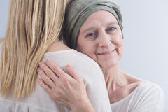 Sick woman and belief in healing. Older sick smiling women with cancer hugging with her young daughter Royalty Free Stock Images