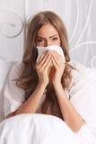 Sick woman blowing her nose. In the bed Royalty Free Stock Image