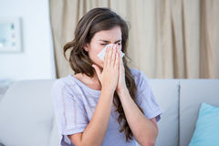 Sick woman blowing her nose. At home in the living room Royalty Free Stock Photography