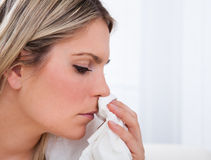 Sick woman blowing her nose Royalty Free Stock Images