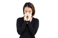 Sick woman blowing her nose with tissue paper Stock Image
