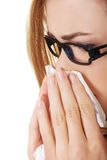 Sick woman blowing her nose Royalty Free Stock Photos