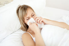 Sick woman blowing lying on her bed. At home Stock Images