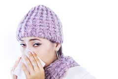 Sick woman blowing nose isolated in white. Sick woman is blowing her nose, wearing beany on isolated white background Stock Photos